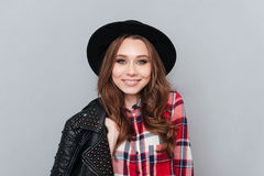 Pretty young woman wearing hat and plaid shirt. Close up portrait of a pretty young woman wearing hat and plaid shirt  over gray background Royalty Free Stock Photo