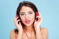 Pretty young woman wearing headphones over blue background Royalty Free Stock Photo