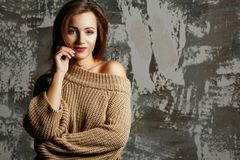 Pretty young woman wearing knitted sweater with naked shoulder, posing with shadows. Empty space stock photo