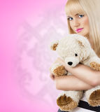 Pretty young woman wearing pajamas embraces teddy bear Royalty Free Stock Photography