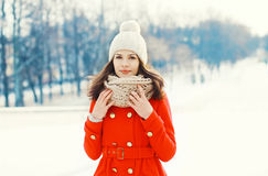 Pretty young woman wearing a red coat, knitted hat and scarf in winter Stock Images