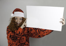 Pretty young woman wearing Santa hat and holding blank sign Royalty Free Stock Images