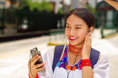 Pretty young woman wearing traditional andean blouse and blue backpack, waiting for bus at outdoors station platform Royalty Free Stock Photography