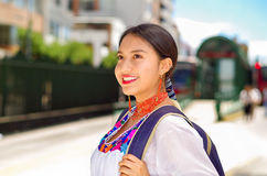 Pretty young woman wearing traditional andean blouse and blue backpack, waiting for bus at outdoors station platform Stock Images