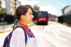Pretty young woman wearing traditional andean blouse and blue backpack, waiting for bus at outdoors station platform Stock Photography