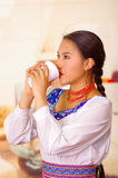 Pretty young woman wearing traditional andean blouse, standing up drinking coffee from white mug Stock Image