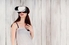A pretty young woman wearing virtual reality glasses, excitedly royalty free stock photos