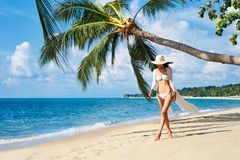 Pretty young woman in white bikini walking barefoot on the sea shore on tropical beach stock photography