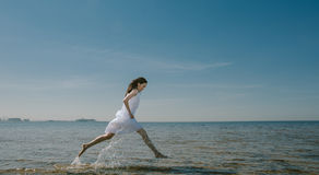 Pretty Young Woman in White Dress Jumping on a Beach Stock Photography