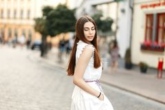 Pretty young woman in white fashionable dress walk in the city. royalty free stock photography