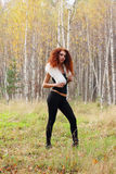 Pretty young woman with white fur poses in autumn forest stock image