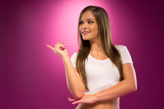 Pretty Young Woman in White Shirt Pointing Right Royalty Free Stock Photo