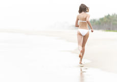 Pretty woman running on wet sand along beach. Stock Photo