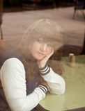 Pretty Young Woman Through Window. An image of a woman sitting at a table and looking out the window, shot through the window Royalty Free Stock Photos
