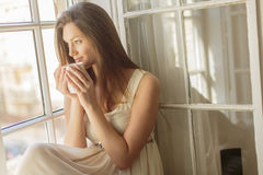 Pretty young woman by window Stock Photos