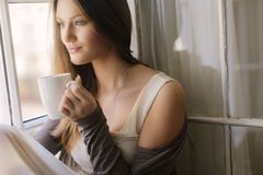 Pretty young woman by the window Stock Images