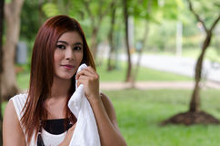 Pretty young woman wiping the sweat. By a white towel Stock Images