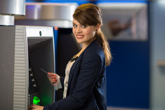 Pretty, young woman withdrawing money from her credit card Royalty Free Stock Images