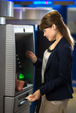 Pretty, young woman withdrawing money from her credit card Stock Photo