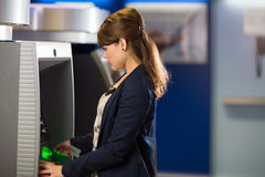 Pretty, young woman withdrawing money from her credit card Stock Photography