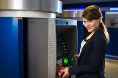 Pretty, young woman withdrawing money from her credit card Stock Images