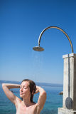 Pretty, young woman woman under shower on the beach Royalty Free Stock Photography