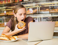 Pretty young woman working at the computer and eat bread. Unheal Royalty Free Stock Image