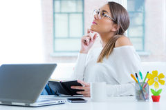 Pretty young woman working in her office. Portrait of pretty young woman working in her office Stock Photography