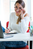 Pretty young woman working in her office. Stock Photos