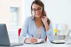 Pretty young woman working in her office. Royalty Free Stock Images