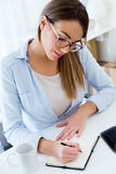 Pretty young woman working in her office. Royalty Free Stock Photos