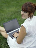 Pretty young woman working on a laptop. Pretty young woman working on her laptop computer outdoors and looking at the camera, smiling Royalty Free Stock Photo
