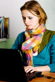 Pretty young woman working at laptop Stock Image