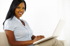 Pretty young woman working on laptop. Portrait of a pretty young black woman working on laptop while resting at home Stock Images