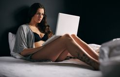 Pretty young woman working on a laptop in bedroom Stock Photo