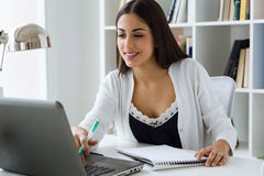Pretty young woman working with laptop in her office. Stock Image