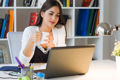 Pretty young woman working with laptop in her office. Royalty Free Stock Image