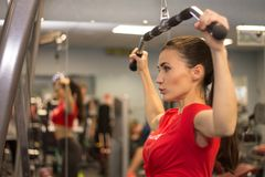 Pretty young woman working out in gym lifting weights. Woman working out in a gym lifting weights by the mirror Stock Images