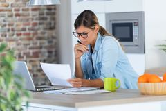Pretty Young Woman Working With Laptop And Documents In The Kitchen At Home Royalty Free Stock Photography