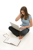 Pretty young woman works on laptop. A pretty young woman, isolated against a white background, works on her laptop royalty free stock images