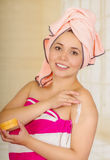 Pretty young woman wrapped with bath towels applying body lotion Royalty Free Stock Photos
