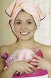 Pretty young woman wrapped with bath towels holding shampoo and loofah sponge Stock Photos