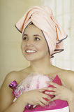 Pretty young woman wrapped with bath towels holding shampoo and loofah sponge Royalty Free Stock Image