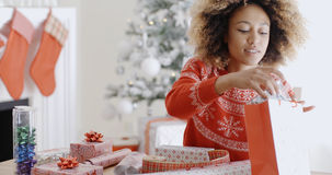 Pretty young woman wrapping Xmas presents Stock Photography