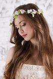 Pretty young woman in wreath with long hair looks down. In white studio stock image