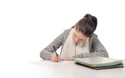 Pretty young woman writing on her desk Stock Image