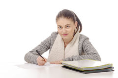 Pretty young woman writing on her desk Stock Photos