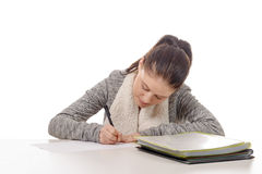 Pretty young woman writing on her desk Stock Images