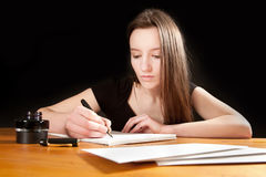 Pretty young woman writing a letter Royalty Free Stock Photos