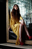 Pretty young woman in yellow fashion long dress Stock Image